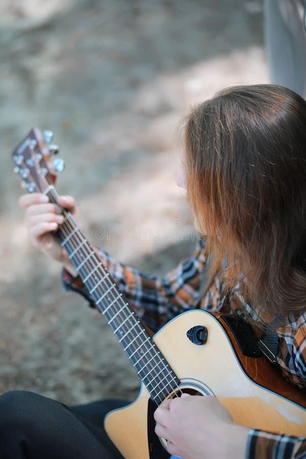 有吉他的人在秋天天 库存照片