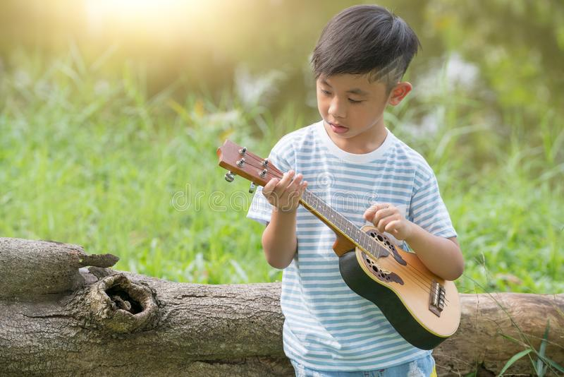 有吉他的可爱的男孩坐在日落,与演奏尤克里里琴的小男孩的音乐概念的草在晴朗的公园 免版税库存图片