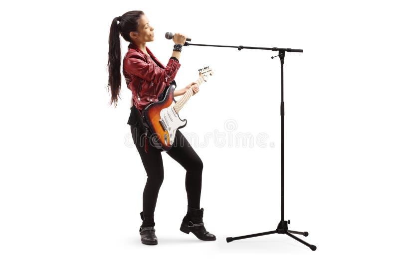 有吉他的女性岩石音乐家唱歌在话筒的 库存图片