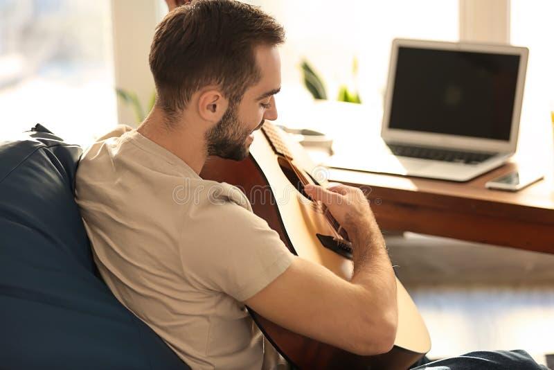 有吉他的年轻人在家坐装豆子小布袋椅子 免版税库存图片