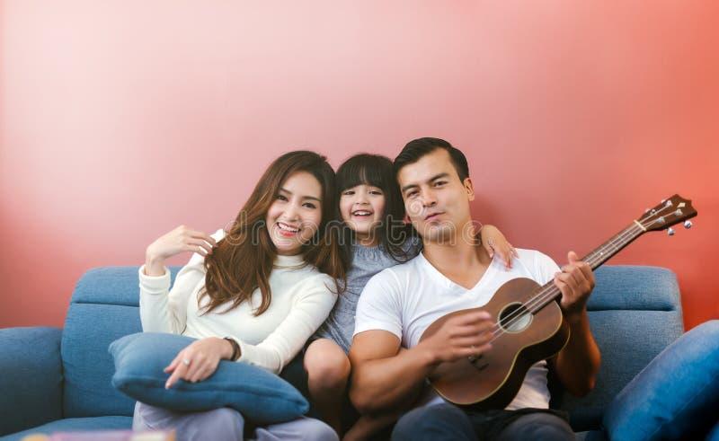 有吉他的幸福家庭在家 父母看见女儿弹吉他 免版税库存照片