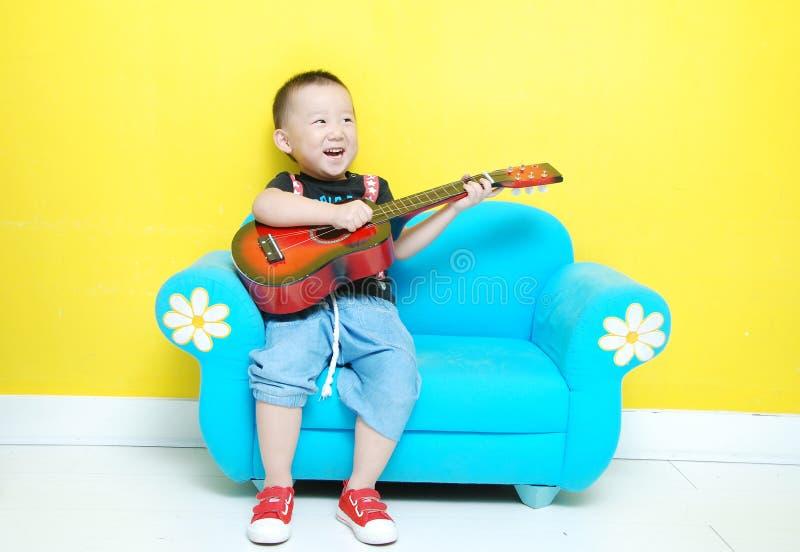 有吉他的英俊的亚裔男孩 库存图片