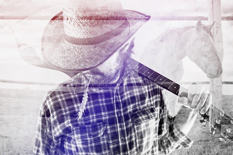 有吉他和草帽的牛仔农夫在马大农场 免版税库存图片