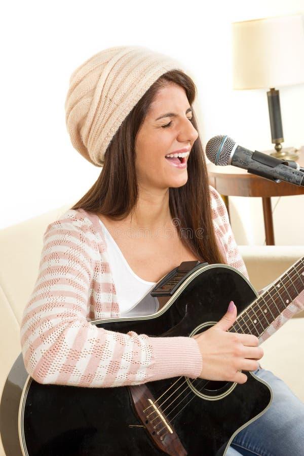 有吉他的女孩唱歌在话筒的 免版税库存照片