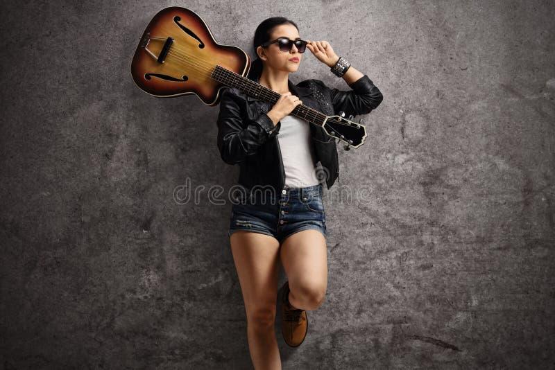 有吉他的少妇在她的倾斜在生锈的灰色wa的肩膀 库存图片