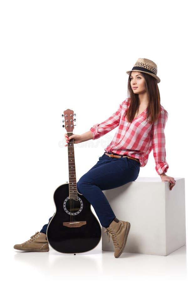 有吉他的少妇音乐家坐立方体 库存图片
