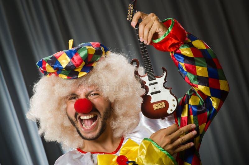 有吉他的恼怒的小丑 免版税库存图片
