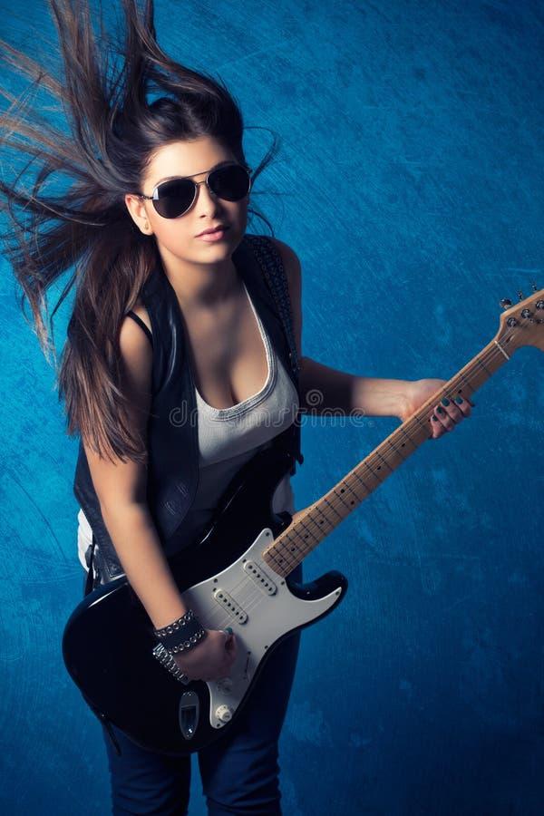 有吉他的美丽的少妇佩带的太阳镜 免版税库存图片