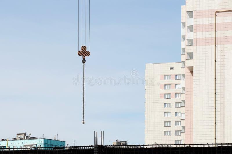 有吊索的起重机勾子一栋居民住房的建筑的 天空蔚蓝,在天空的起重机 图库摄影