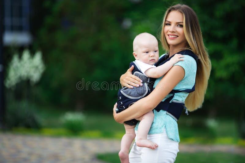 有吊索的走在绿色公园的男婴的俏丽的母亲 免版税库存图片