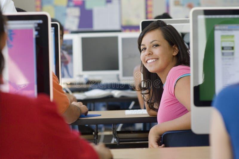 有同学的女学生在计算机实验室 免版税库存图片