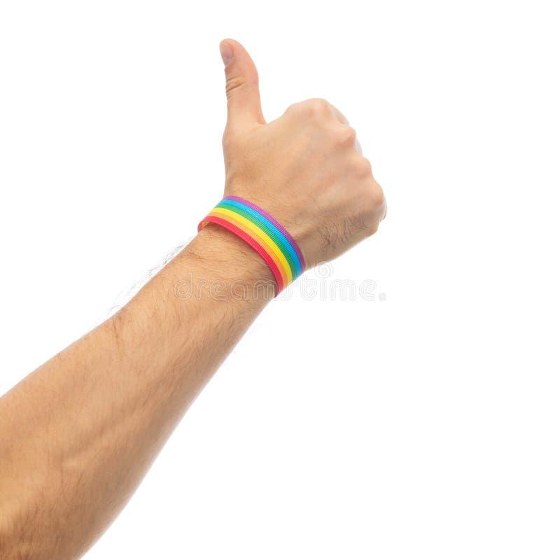 有同性恋自豪日彩虹袖口的手显示拇指 免版税库存照片