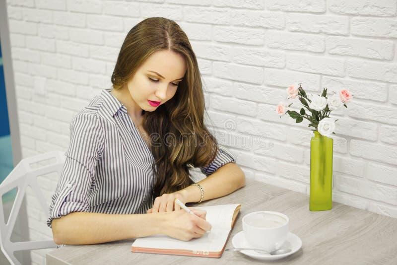 有同情心的女孩候宰栏和文字在写生簿 免版税库存照片