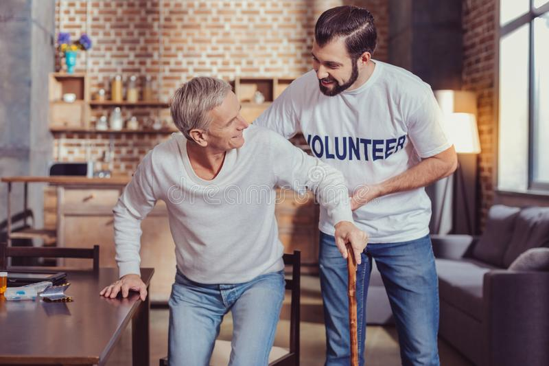 有同情心的宜人退休的志愿者身分和帮助 库存图片