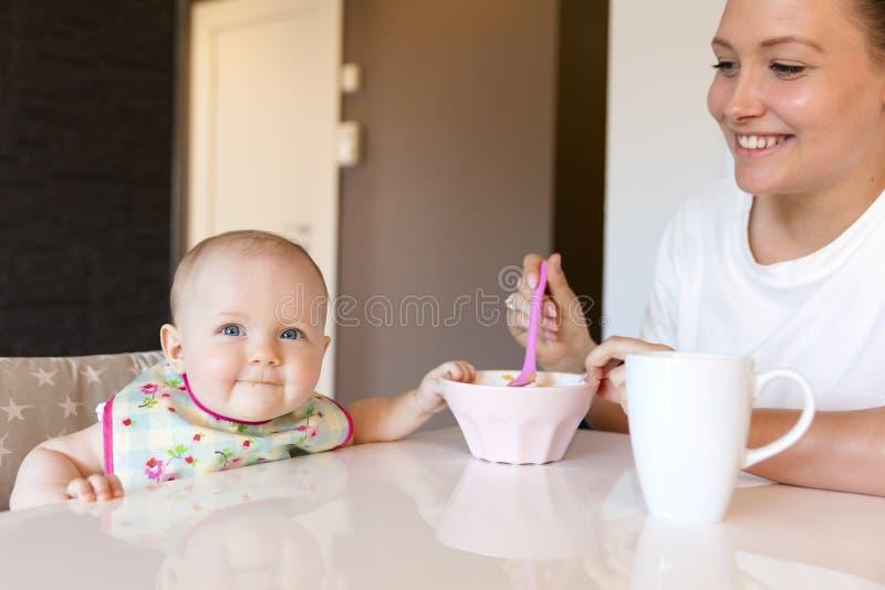 有同情心的年轻母亲喂养她微笑的女婴 免版税库存照片
