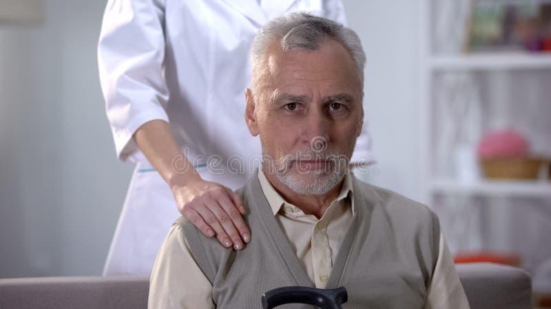 有后边拐棍开会的资深人在沙发在老人院,护士 免版税库存图片