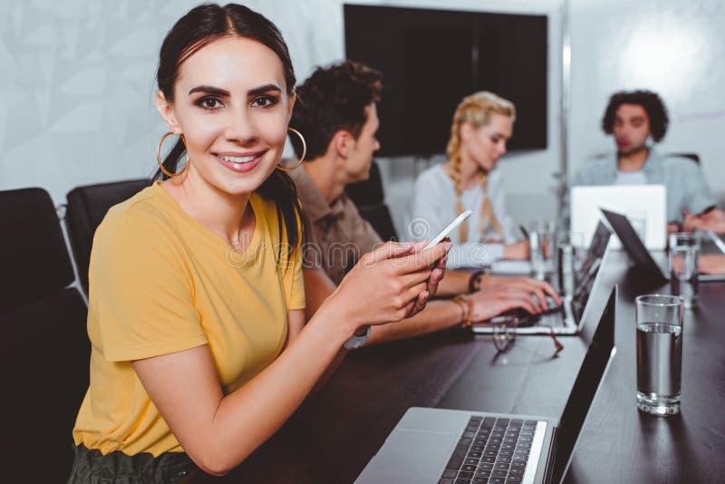 有后边智能手机的微笑的年轻女实业家和她的伙伴有讨论在现代 免版税库存照片