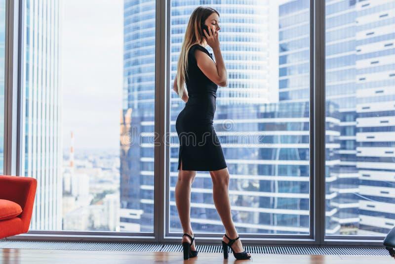 有后面观点的成功的女实业家看窗口有都市风景视图的电话交谈 库存图片