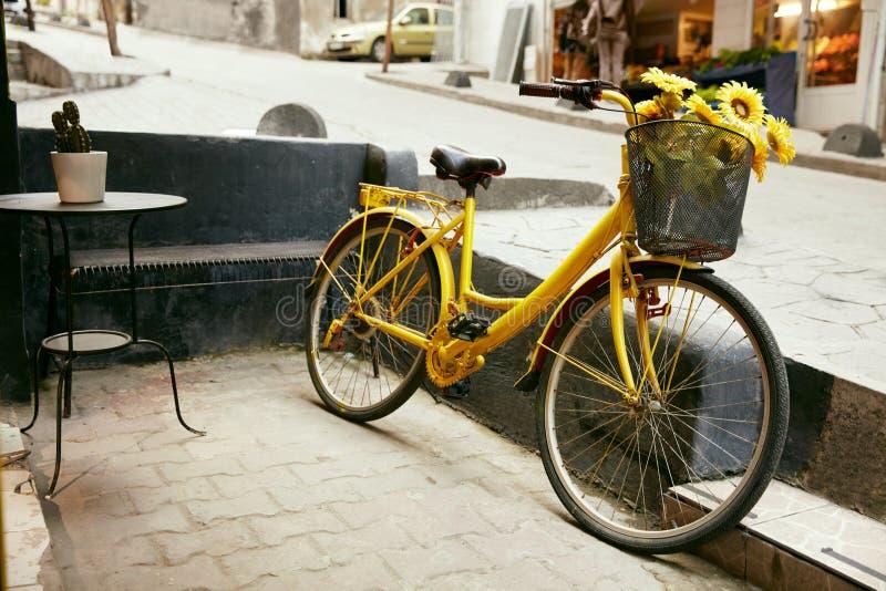 有向日葵篮子的黄色自行车在城市街道的 免版税库存图片