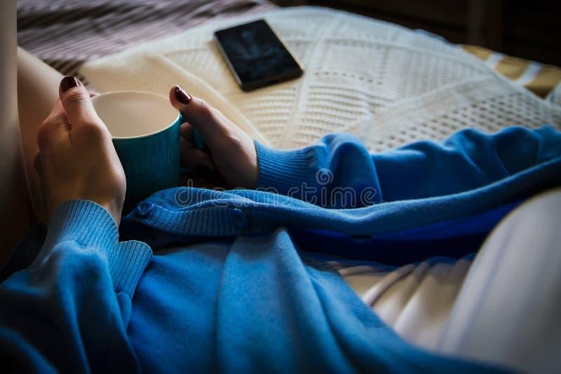 有听到音乐的一杯茶的妇女在床上 库存图片