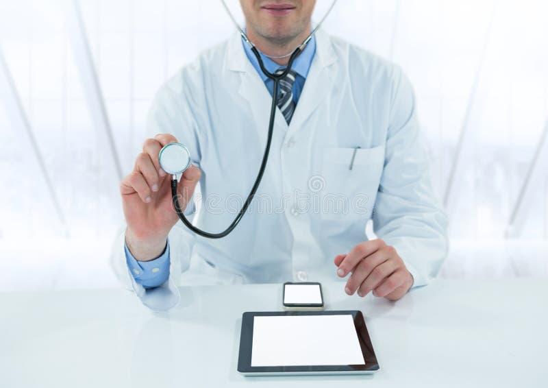 有听诊器和设备的医生在反对模糊的窗口的书桌 库存图片