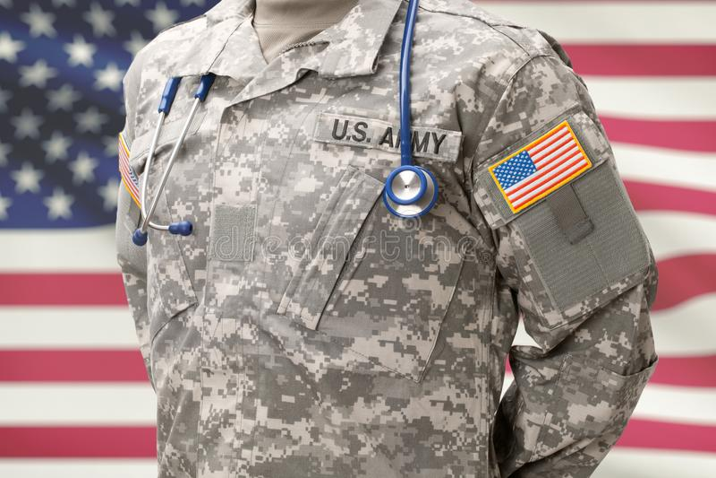 有听诊器在他的脖子和美国旗子的美国陆军医生在背景 库存照片