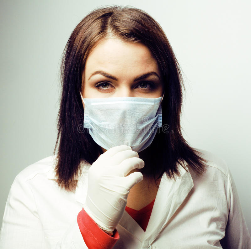 有听诊器微笑的,佩带的手套和面具的年轻俏丽的深色的妇女医生在面孔,生活方式真正的人民 库存图片