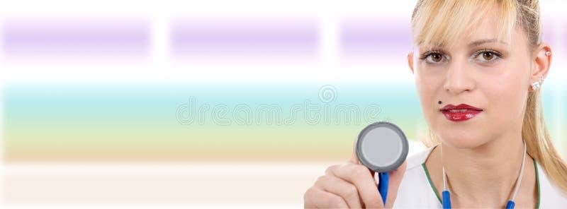 有听诊器的俏丽的年轻白肤金发的妇女医生 免版税库存照片