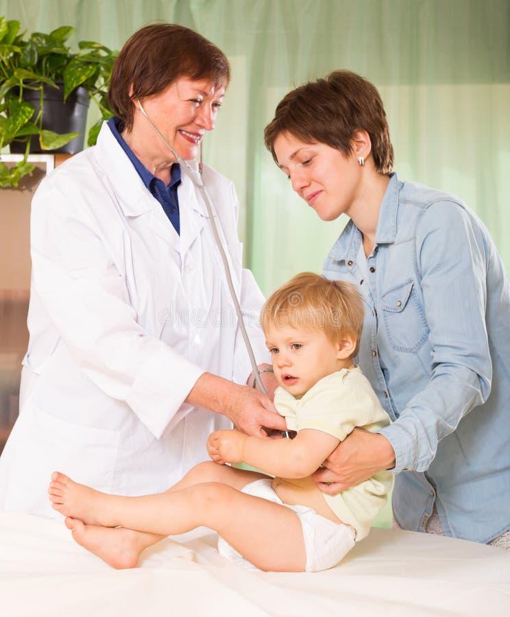 有听诊器的儿科医生医生审查的女婴 图库摄影