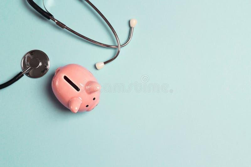 有听诊器的存钱罐在蓝色背景 与拷贝空间的顶视图 库存图片