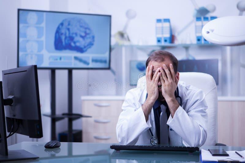 有听诊器的年轻男性开业医生在他的脖子疲乏的ater附近每辛苦在实验室里 库存照片