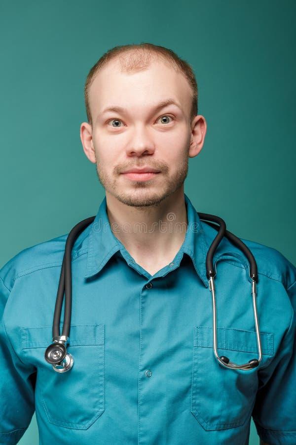 有听诊器的男性医生微笑和看在蓝色背景的照相机 免版税库存图片