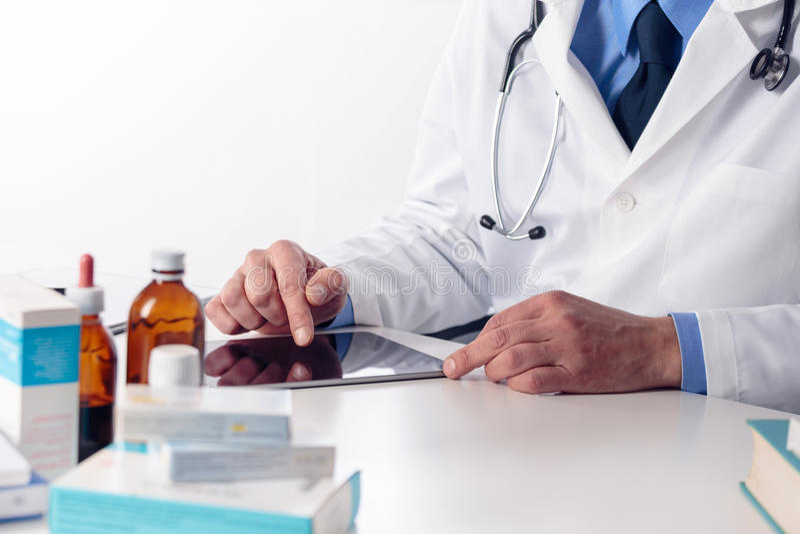 有听诊器的男性医生` s手在使用数字式桌的书桌 免版税库存照片