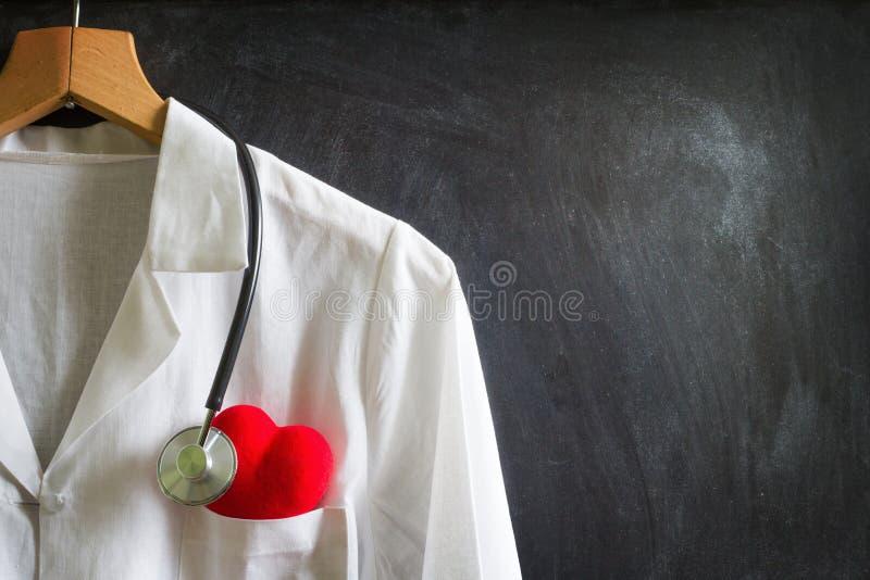有听诊器的医生外套在黑板 免版税库存照片