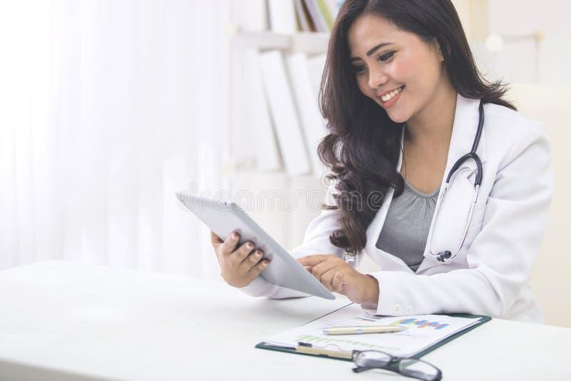 有听诊器的医生妇女使用片剂个人计算机 免版税库存图片