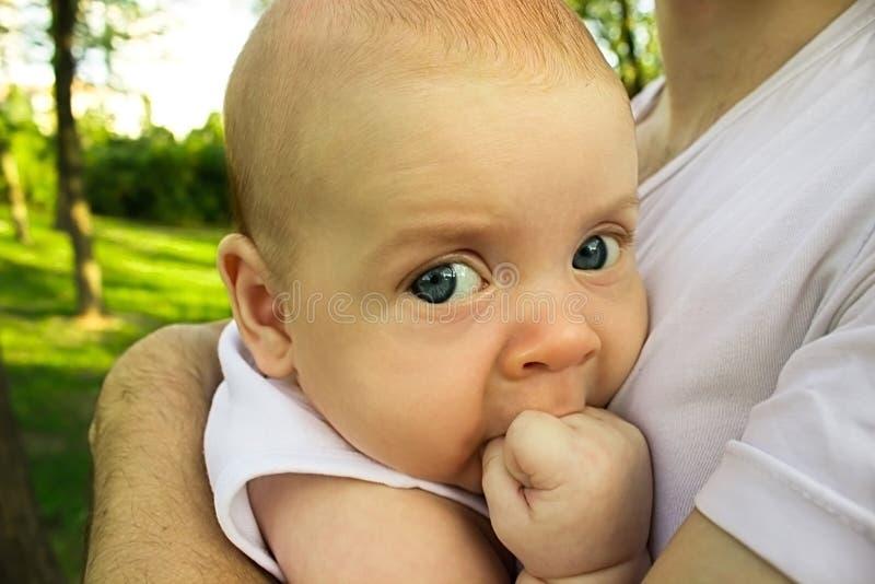 有吮他在嘴的大蓝眼睛的小男婴小的拳头 说谎在父亲` s胳膊 库存照片