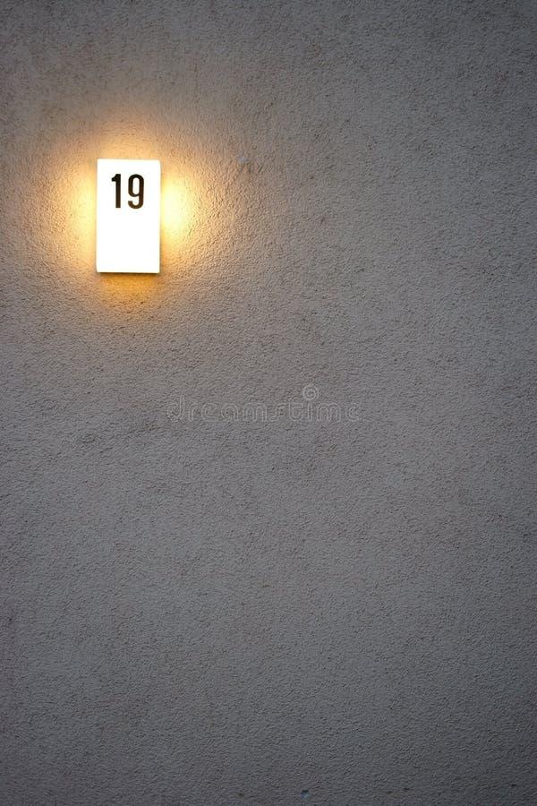 有启发性房子号码板材在晚上 免版税库存照片