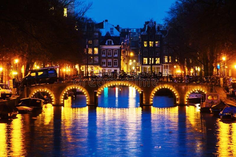 有启发性桥梁和历史大厦在阿姆斯特丹,荷兰在晚上 库存图片