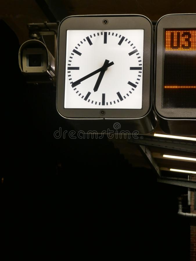 有启发性驻地时钟,在地铁的平台的晚上 免版税库存照片