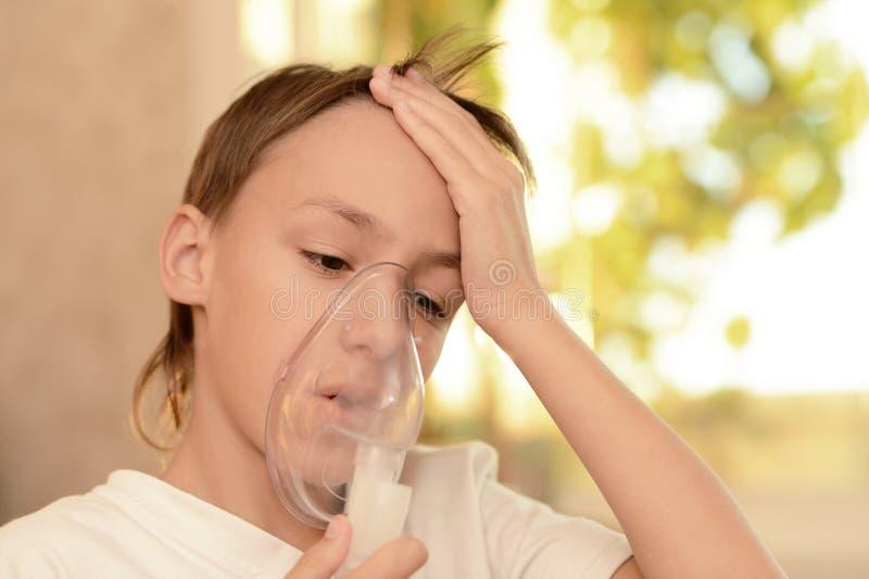 有吸入器的病的男孩 免版税库存图片