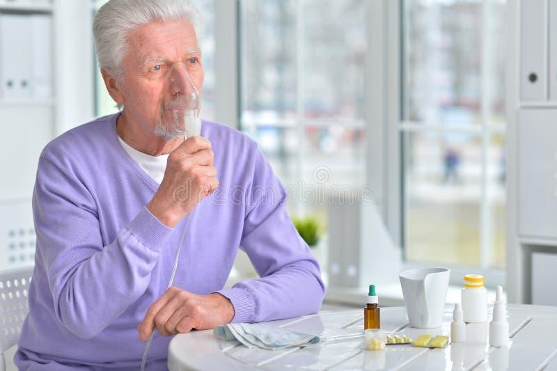 有吸入器的老人 免版税库存照片