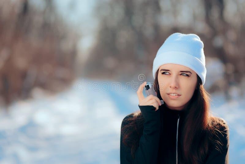 有吸入器遭受的哮喘病发作的妇女在冬天 库存图片