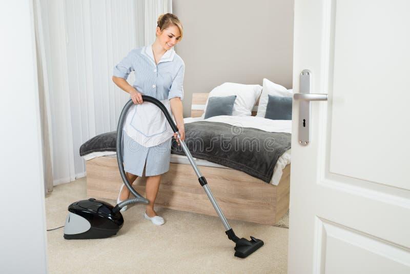 有吸尘器的佣人在旅馆客房 图库摄影