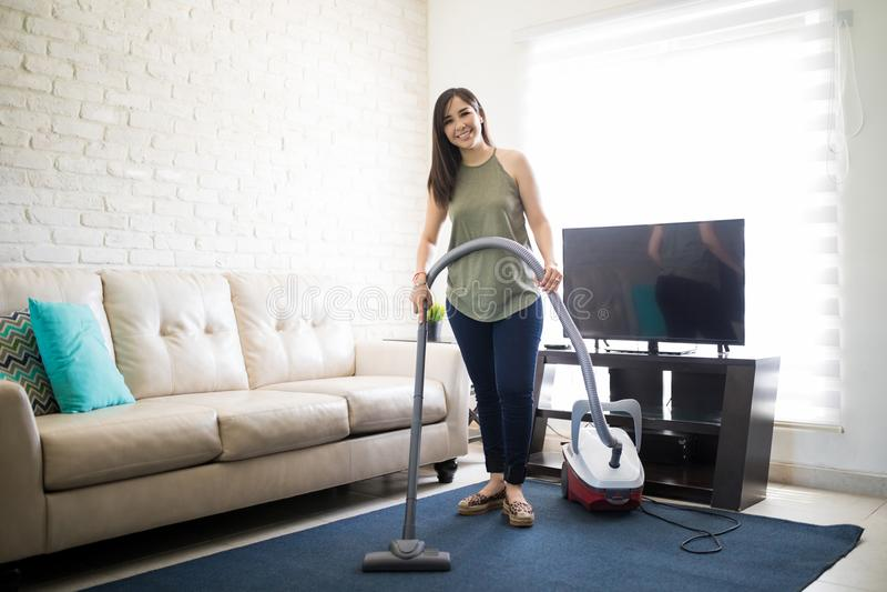 有吸尘器的少妇hoovering的地毯 图库摄影