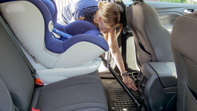 有吸尘器的年轻女性司机清洁汽车 图库摄影