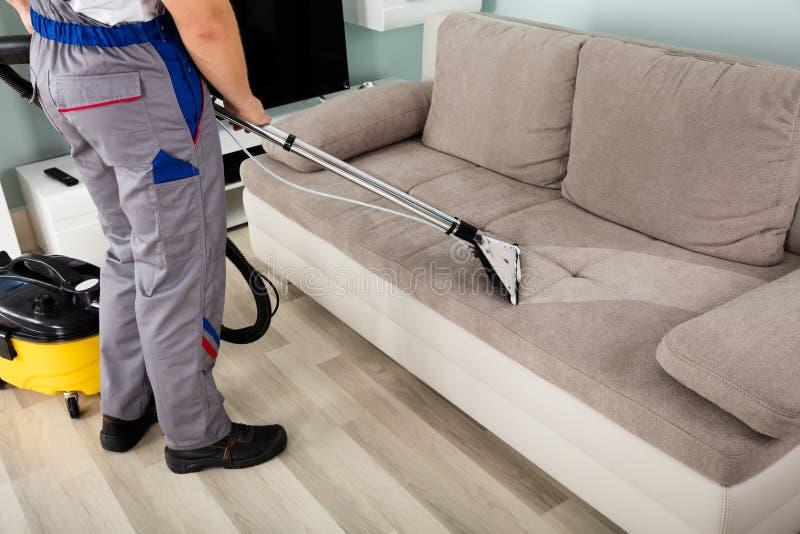 有吸尘器的男性工作者清洁沙发 库存照片