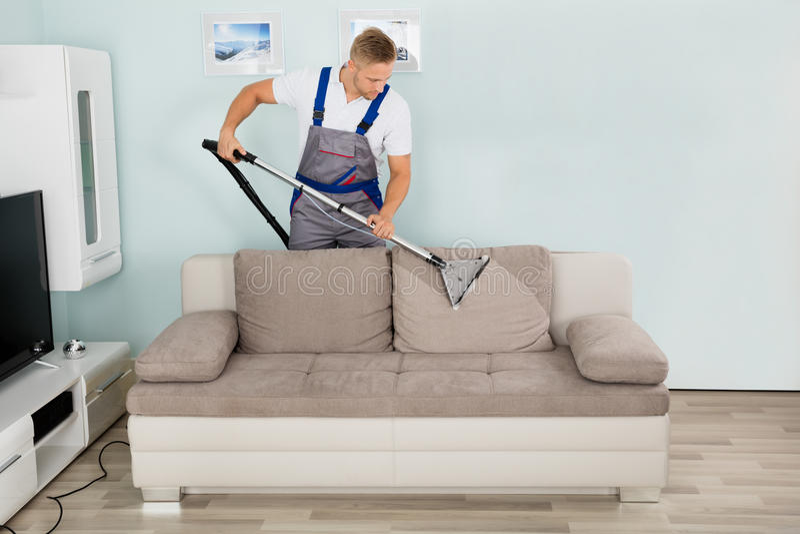 有吸尘器的男性工作者清洁沙发 图库摄影