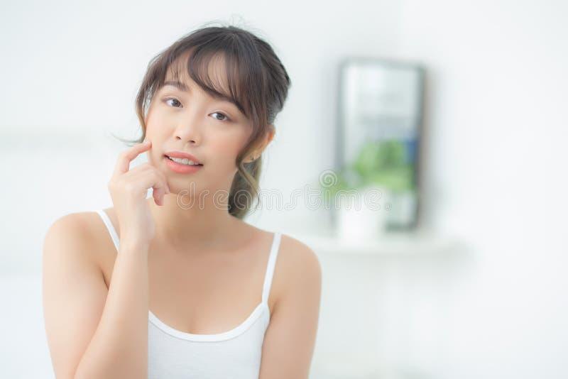 有吸引力化妆用品、女孩手接触的面颊和的微笑画象美好的亚洲妇女构成  库存图片
