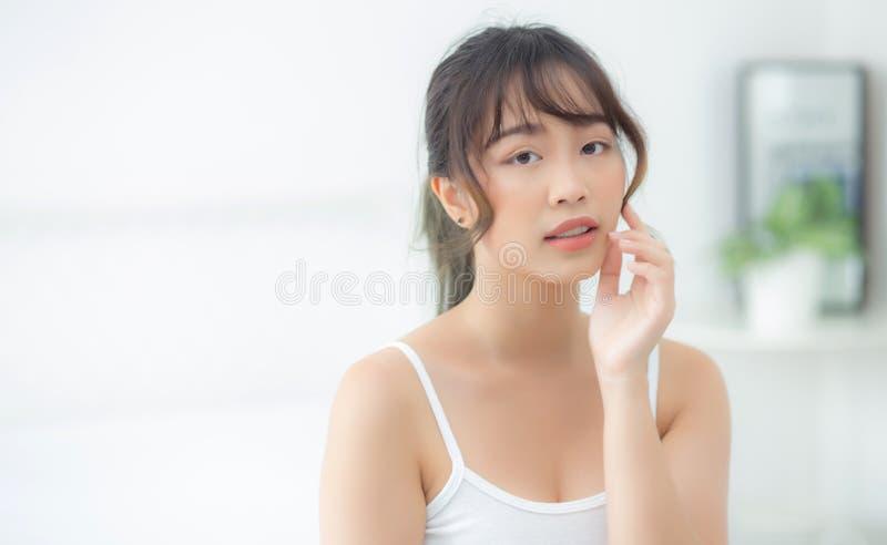 有吸引力化妆用品、女孩手接触的面颊和的微笑画象美好的亚洲妇女构成  图库摄影