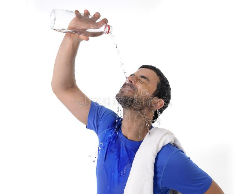 年轻有吸引力和体育运动人用尽了在他的面孔的倾吐的水 库存图片